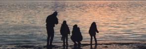 Familie ser solnedgang p� standen